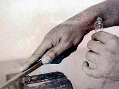 Móvil perpetuo, 2001 / Fotografía en blanco y negro / Objeto de metal y vidrio, con sudor y limadura de moneda / 15 x 3,5 x 4 cm